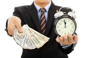 businessman holding money and clock. time is money concept ** Note: Shallow depth of field